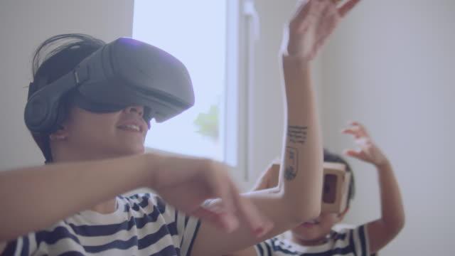 vidéos et rushes de famille asiatique heureuse avec le casque vr explorant la réalité virtuelle- - casque