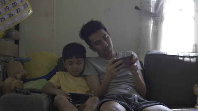 happy asian father and son using smartphone to learning together - genderblend stock videos & royalty-free footage