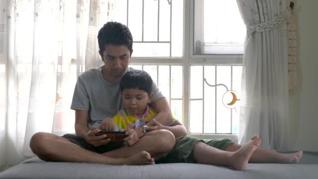 vídeos y material grabado en eventos de stock de feliz padre asiático e hijo usando el teléfono inteligente para aprender juntos - intergénero