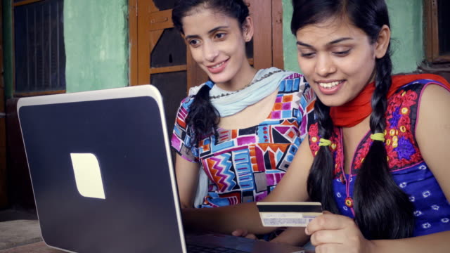Happy Asian female friends doing online shopping at home.