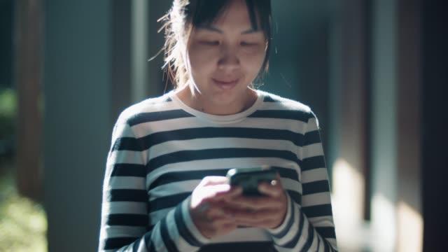glückliche asiatische frau mit telefon zum textieren - connection in process stock-videos und b-roll-filmmaterial