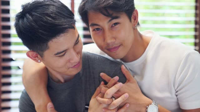 a happy asian gay couple in love hugging each other, holding hands. homosexual love intimacy romantic romance - front view stock videos & royalty-free footage