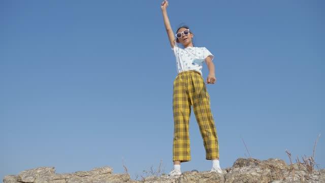 glückliche asiatische mädchen tanzen auf dem gipfel des berges gegen blauen himmel für virale video-inhalte in tiktok anwendung, lifestyle-konzept. - content stock-videos und b-roll-filmmaterial