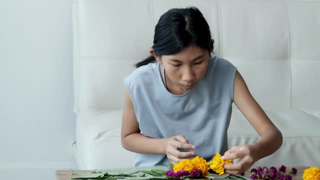 happy asian girl flower arrangement for krathong (make from banana leafs and flowers for floating in the rivers for pray and thank you) together at home, preparing for the night time. - flower arrangement stock videos & royalty-free footage