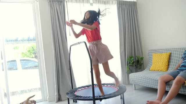 happy asian girl jumping on mini trampoline at home and her brother is playing with dog near window, lifestyle concept. - overweight dog stock videos & royalty-free footage