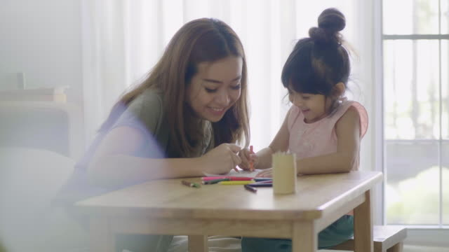 happy asian girl painting with crayon with her mother in living room at home. - home improvement stock videos & royalty-free footage