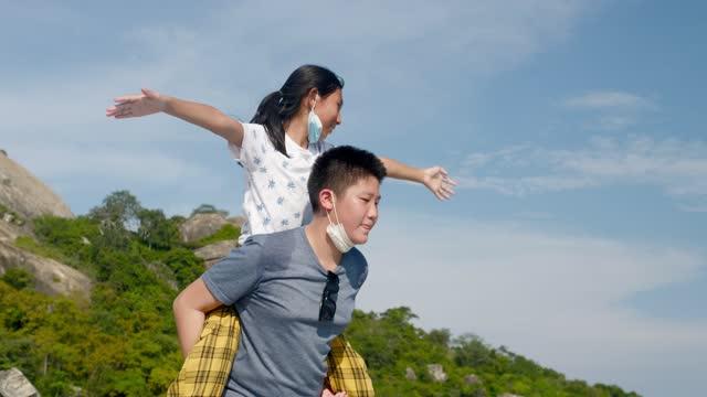 vídeos y material grabado en eventos de stock de feliz chica asiática piggybacking su hermano contra el cielo y la vista al mar en un día soleado durante su viaje, cámara lenta. - carrying