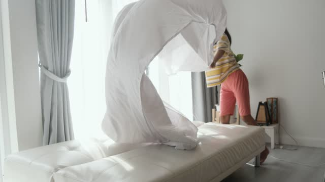 happy asian girl setup her bed sheet by herself in the morning with sunlights at home, lifestyle concept. - sheet bedding stock videos & royalty-free footage
