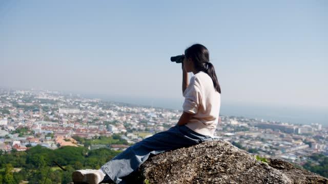 晴れた日に山の頂上の眺めを見て双眼鏡を使用して幸せなアジアの女の子、ライフスタイルの概念。 - 双眼鏡点の映像素材/bロール