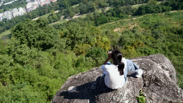 stockvideo's en b-roll-footage met gelukkig aziatisch meisje dat verrekijker gebruikt die mening op de bovenkant van berg in zonnige dag, levensstijlconcept bekijkt. - sunny