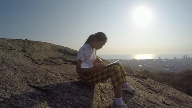 happy asian girl using digital tablet while sitting on the mountain viewpoint in the morning, lifestyle concept. - primary age child stock videos & royalty-free footage