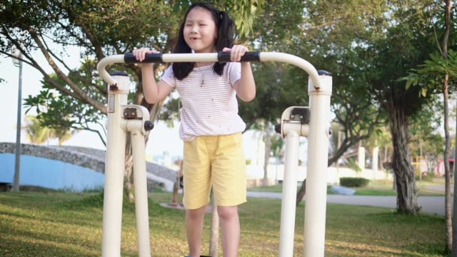 happy asian girl using exercise equipment in the park outdoor, slow motion. - moulding trim stock videos & royalty-free footage