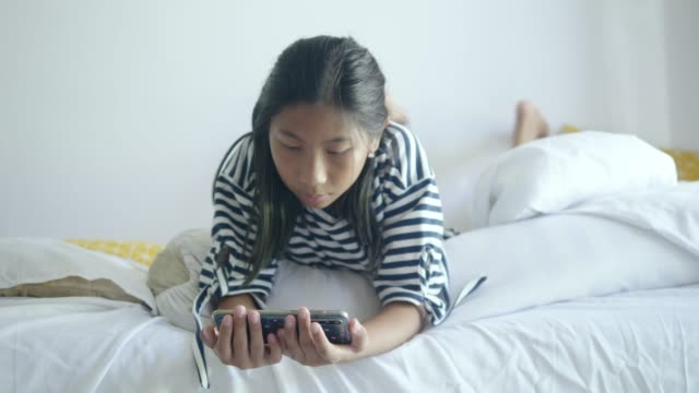 happy asian girl using smartphone and lying on bed at home, lifestyle concept. - duvet stock videos & royalty-free footage
