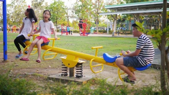 glückliche asiatische mädchen spielen wippe auf dem spielplatz zusammen. - wippe stock-videos und b-roll-filmmaterial