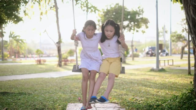 happy asian girls playing swing together, slow motion. - altalena video stock e b–roll