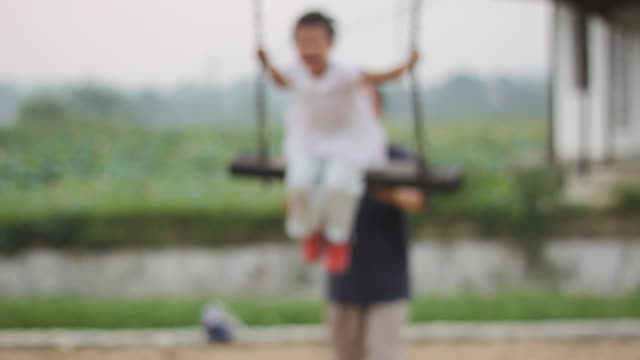 Happy asian kid swinging yelling, grandpa pushing the swing, loopable.