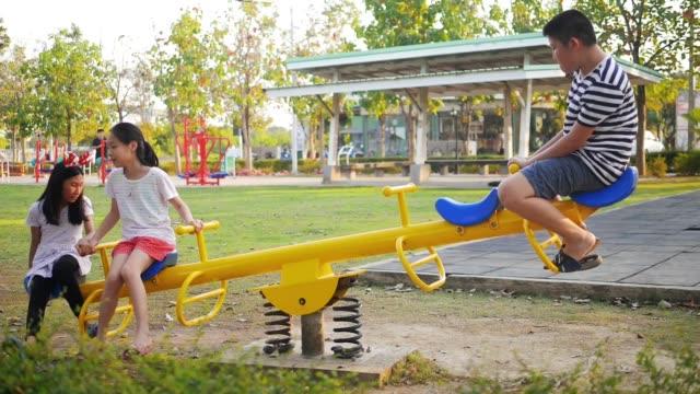 glückliche asiatische kinder spielen wippe auf dem spielplatz zusammen, zeitlupe. - wippe stock-videos und b-roll-filmmaterial