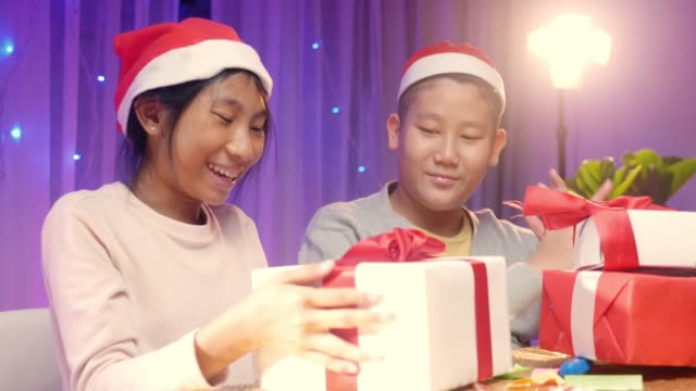 happy asian kids wearing santa hat and preparing gift boxes and card for family party with christmas light background. - christmas card stock videos & royalty-free footage