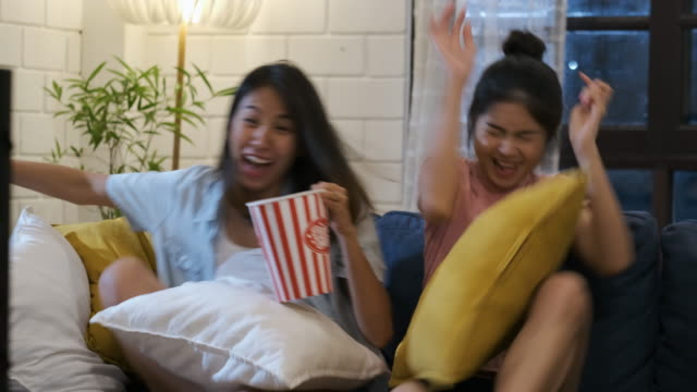 happy asian lesbian couple watching scary movie on television together and jump out at sofa in night time at home with chill ing emotion.woman friendship lifestyle - video stock videos & royalty-free footage