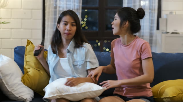 happy asian lesbian couple watching television together and fun fight for grab remote control  on sofa in night time at home with chill ing emotion.woman friendship lifestyle - reaching stock videos & royalty-free footage