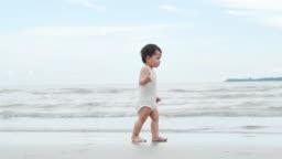 Happy asian little baby boy son learning to walk on tropical beach having fun along edge of sunset sea surf on sand beach.