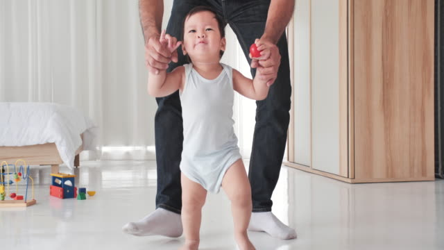 happy asian little baby learning to walk with father help at home.family, child, single father, childhood and parenthood concept.baby's first steps - primi passi video stock e b–roll