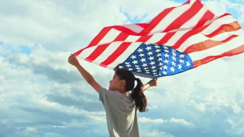 felice bambina asiatica con bandiera americana usa festeggia il 4 luglio - memorial video stock e b–roll