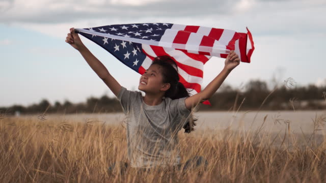 happy asian little girl with american flag usa celebrate 4th of july - circa 4th century stock videos & royalty-free footage