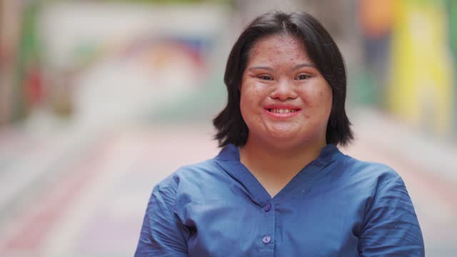 happy asian malay autism down syndrome female  looking at camera smiling in city street - satisfaction stock videos & royalty-free footage