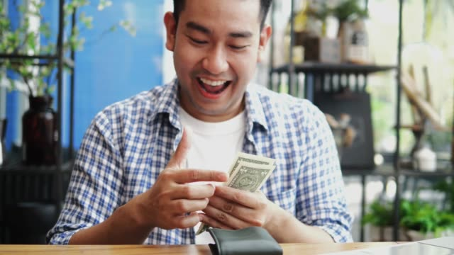 happy asian man counting us dollars in his hands, financial concept. - wallet stock videos & royalty-free footage