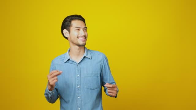 vídeos y material grabado en eventos de stock de hombre asiático feliz bailando sobre fondo amarillo en el estudio, tiro en la cabeza, resolución 4k - gesticular