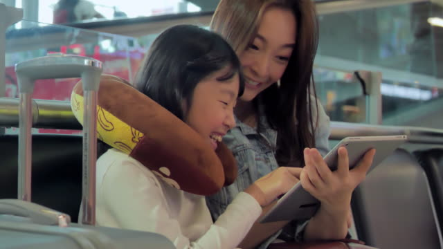 happy asian mother and daughter sitting in airport waiting for boarding and playing on a tablet.travel,journey,global,lifestyle,holidays,technology concept.south east and east asia: at the airport - east asian ethnicity video stock e b–roll