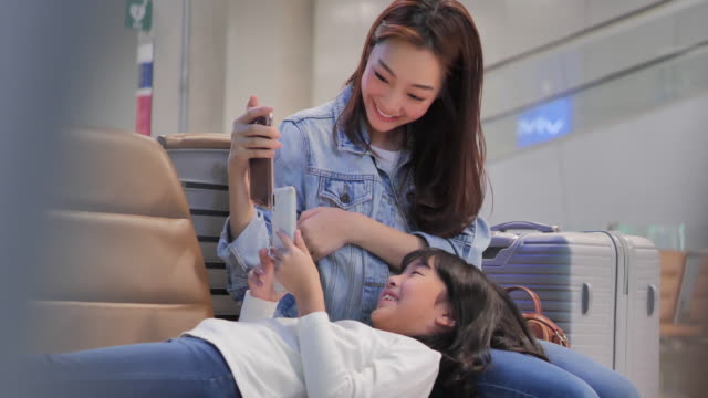 happy asian mother and daughter sitting in airport waiting for boarding and playing on smartphone.travel,journey,global,lifestyle,holidays,technology concept.south east and east asia: at the airport - east asian ethnicity video stock e b–roll