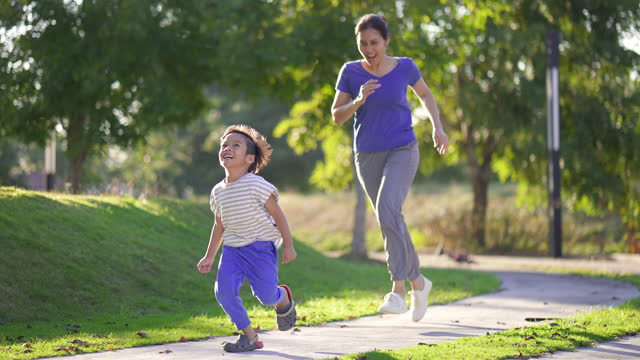 happy asian mother and son jogging in park, outdoor. - lush stock videos & royalty-free footage