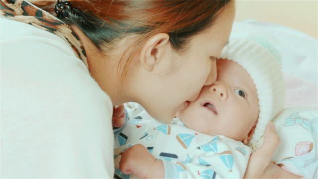 ハッピーなアジアの母親にキスをすると、頬を彼女のミックスレースかわいい小さな新生児の女の子の彼女のベッドルーム - ユーラシアエスニシティ点の映像素材/bロール