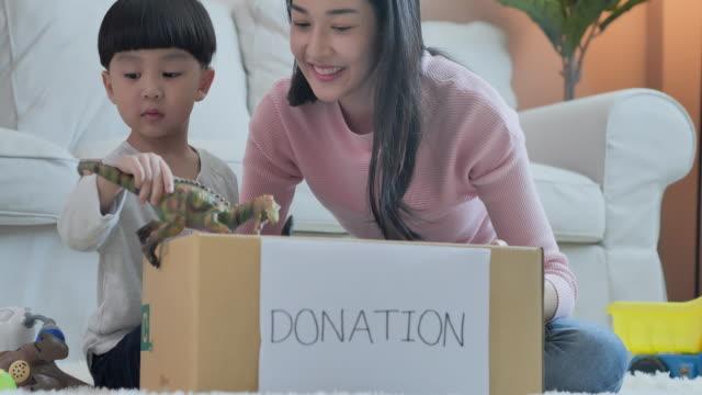 felice madre asiatica che insegna al figlio piccolo sulla sostenibilità come imballare i giocattoli in una scatola di doni a casa, insegnare / imparare a conoscere il concetto di donazione. - altruismo video stock e b–roll