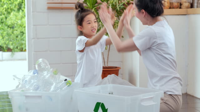 happy asian mother teaching little girl daughter about sustainability how to recycle household waste at home,teaching/learning about reusable products and zero waste.family, education,recycling in daily life - chinese ethnicity stock videos & royalty-free footage