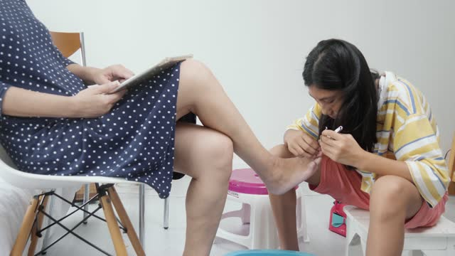 happy asian mother using digital tablet while her daughter cleaning her feet before toenails painting, lifestyle concept. - painting toenails stock videos & royalty-free footage