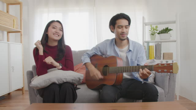happy asian musician  playing and dancing online in domestic room,leisure activities at home during the corona virus epidemic - musician stock videos & royalty-free footage