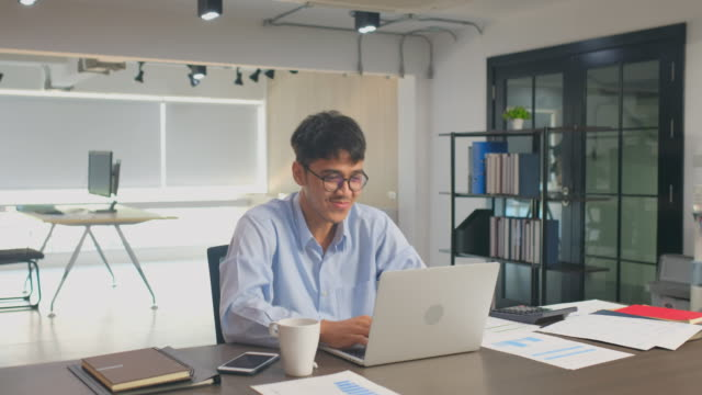 vídeos de stock e filmes b-roll de happy asian office man reading good news on laptop computer smiling and arms rised at his desk in office, achieve success and celebration emotion - encontrar