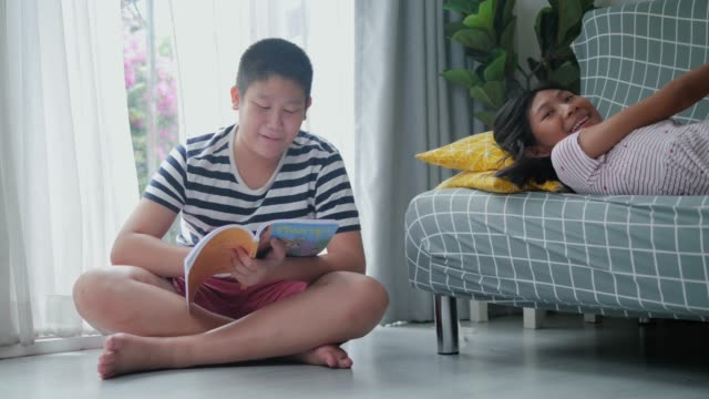 happy asian preteen boy and his sister reading books at home, talking and laughing together. - pre adolescent child stock videos & royalty-free footage