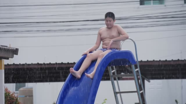 happy asian preteen boy sitting on slider in rainy day, slow motion. - navel stock videos & royalty-free footage