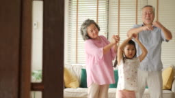 Happy asian senior couple dancing together with their granddaughters at home. Senior lifestyle family concept.