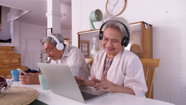 happy asian senior couple using laptop computer and mobile phone while enjoy listening to music at home, family relaxing and spending time together at home, retirement people and lifestyle concept - music stock videos & royalty-free footage