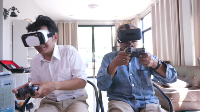 happy asian senior father and his adult son enjoy playing video games together with virtual reality glasses in living room at home - malaysian ethnicity stock videos & royalty-free footage