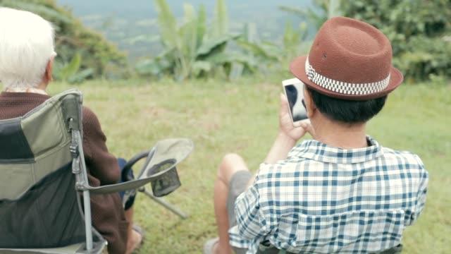 vídeos de stock e filmes b-roll de happy asian senior man using the mobile phone, slow motion - idoso na internet
