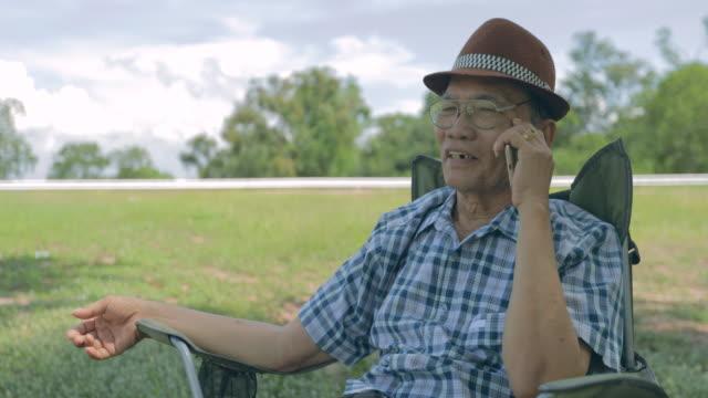 vídeos de stock e filmes b-roll de happy asian senior man using the mobile phone - idoso na internet