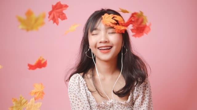 happy asian teenager girl wearing using earphone and playing with dropping maple leafs on pink background.  slow motion. - viraggio monocromo video stock e b–roll