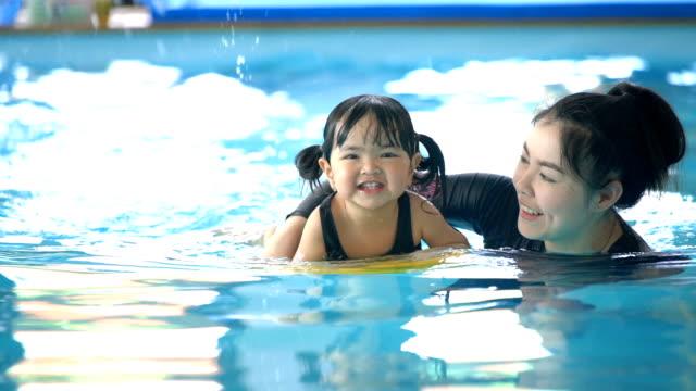 SLO MO glücklich asiatischen kleinkind schwimmen, Kamera