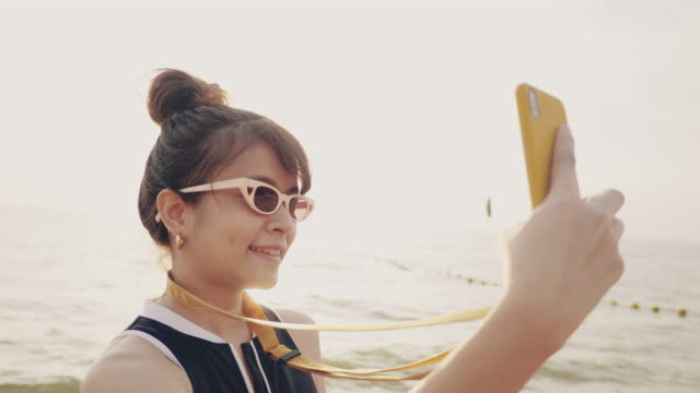 happy asian woman beach taking social media selfie with sunset beach. - sunny stock videos & royalty-free footage